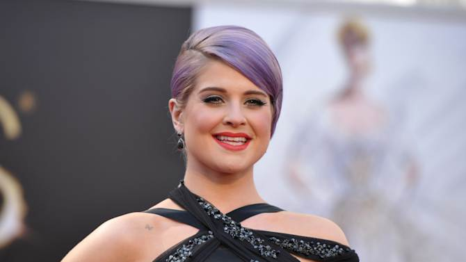 """FILE - In this Sunday, Feb. 24, 2013 file photo, TV personality Kelly Osbourne arrives at the 85th Academy Awards at the Dolby Theatre in Los Angeles.  Osbourne has been hospitalized after fainting on the set of E!'s """"Fashion Police."""" A spokeswoman for Osbourne told the cable network Thursday, March 7, 2013, that the 28-year-old TV personality is awake, alert and in stable condition, and she will be staying overnight for observation as a precautionary measure.  (Photo by John Shearer/Invision/AP, File)"""