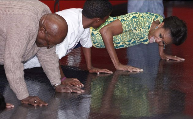 U.S. first lady Michelle Obama does push-ups with Archbishop Desmond Tutu as they participate in youth activities raising awareness for HIV prevention, at Cape Town Stadium in Cape Town