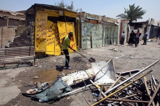 An Iraqi youth removes debris from the site of a roadside bomb in Baghdad's Karrada district on June 13. Shootings and bombings in Baghdad and north of the capital killed three people on Monday, including a policeman, security and medical officials said
