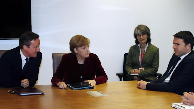 British Prime Minister David Cameron, left, and German Chancellor Angela Merkel, second left, speak with Italian Prime Minister Matteo Renzi, right, during a meeting at an EU summit in Brussels on Thursday, March 6, 2014. EU heads of state meet Thursday in emergency session to discuss the situation in Ukraine. (AP Photo/Michel Euler, Pool)