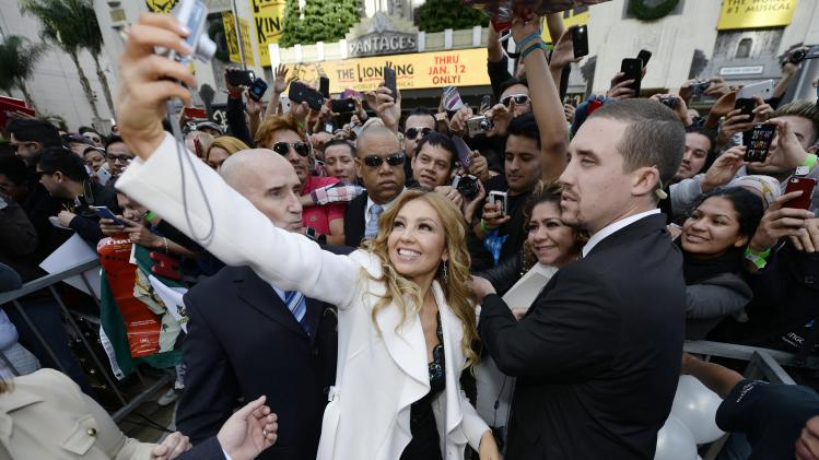 Performer Thalia uses a fan's camera to photograph herself after unveiling of her star on the Hollywood Walk of Fame n Hollywood California