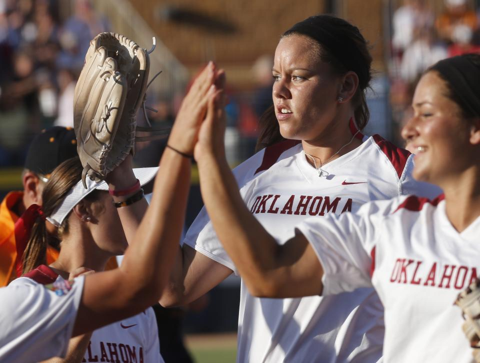 Oklahoma pitcher Keilani Ricketts gets high fives from her teammates after pitching against Tennessee in the first inning of the first game of the best of three Women's College World Series NCAA softball championship series in Oklahoma City, Monday, June 3, 2013. (AP Photo/Sue Ogrocki)