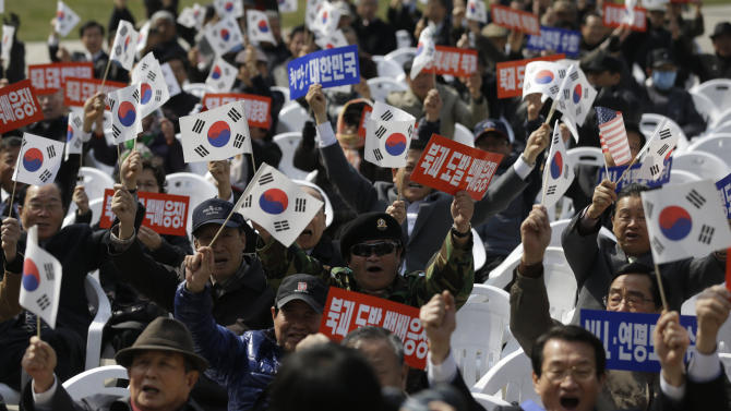 "South Korean protesters shout slogans during a rally to mark the third anniversary of the sinking of South Korean naval ship ""Cheonan"" which killed 46 South Korean sailors, in Seoul, South Korea, Tuesday, March 26, 2013. An explosion ripped apart the 1,200-ton warship, killing 46 sailors near the maritime border with North Korea in 2010. The placards read: ""Punishment, North Korea's provocation."" (AP Photo/Lee Jin-man)"
