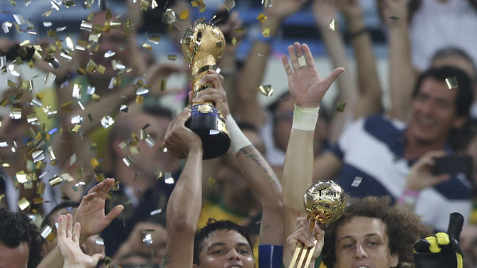Surrounded by teammates Brazil's Thiago Silva, center back, lifts the trophy after the soccer Confederations Cup final between Brazil and Spain at the Maracana stadium in Rio de Janeiro, Brazil, Sunday, June 30, 2013. Brazil won 3-0. (AP Photo/Andre Penner)