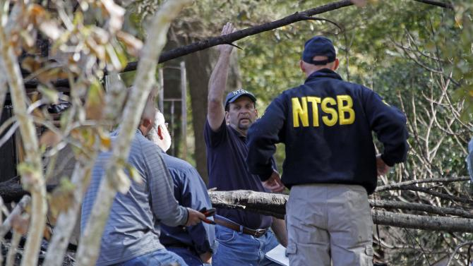 NTSB investigator Paul Cox gestures to local investigators Wednesday, Nov. 14, 2012, underneath some trees that a small plane is believed to have clipped as it crashed Tuesday evening into a home in west Jackson, Miss. The home caught fire but was contained by fire fighters. It's resident escaped with injuries, however the local authorities confirmed the plane's passengers were dead.  (AP Photo/Rogelio V. Solis)