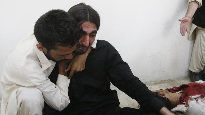 A person comforts a man who mourns the death of a family member who was killed in a bomb blast near a rally by the Awami National Party that killed at least five people, in Quetta, Pakistan, Friday, July 13, 2012. (AP Photo/Arshad Butt)