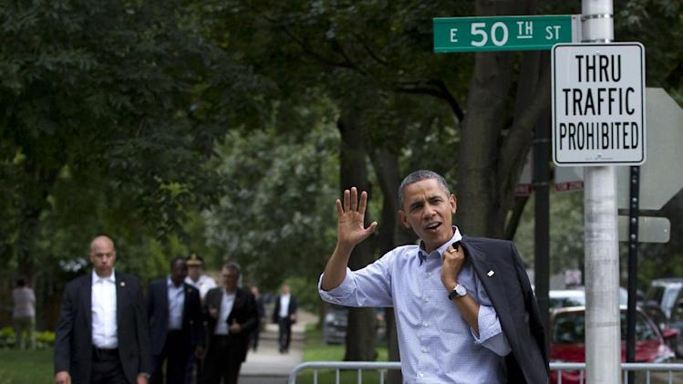 President Barack Obama waves as he walks through his Hyde Park neighborhood to a campaign event, Sunday, Aug. 12, 2012, in Chicago. (AP Photo/Carolyn Kaster)