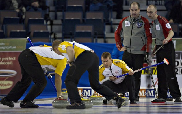 Manitoba skip Stoughton shouts to teammates to sweep as Northwest Territories skip Koe and Nauggler watch during play at the Canadian Men's Curling Championships  in Edmonton