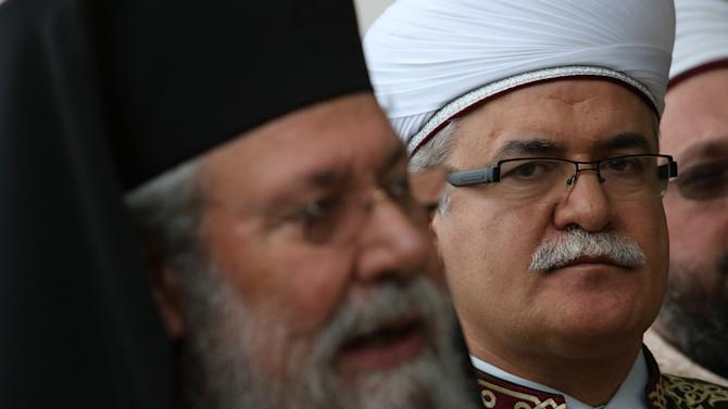 Turkish Cypriot religious leader Mufti Talip Atalay looks on as Greek Cypriot Orthodox religious leader Archbishop Chrysostomos II speaks to the media