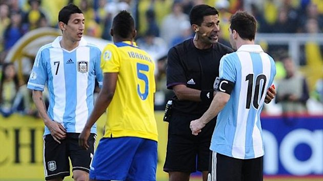 Argentine Lionel Messi (R) argues with Paraguayan referee Enrique Caceres alongside team-mate Angel Di Maria (L) and Ecuadorean Alex Ibarra (AFP)