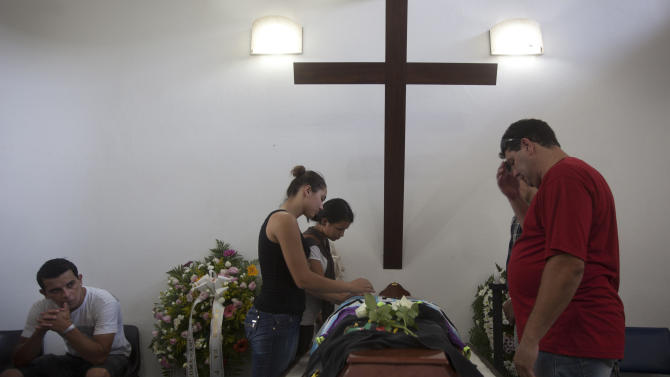 People attend the funeral of Gustavo Goncalves, the most recent victim of the Kiss nightclub fatal fire, raising the death toll to 235, in Santa Maria, Brazil, Wednesday, Jan. 30, 2013. A fast-moving fire roared through the crowded, windowless nightclub in this southern Brazilian city early Sunday. The first funeral services were held Monday for the victims. Most of the dead were college students 18 to 21 years old. (AP Photo/Felipe Dana)
