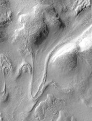 Orbital photos from NASA Mars Reconnaissance Orbiter shows lobate-shaped glacier flowing down the north inner wall of crater Greg, on the planet Mars. The wall slopes downhill to the south (bottom) part of the frame. Note how flow lines drape a