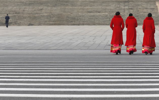 Hotel guides walk at Tiananmen Square near Great Hall of People during of fourth plenary meeting of National People's Congress in Beijing