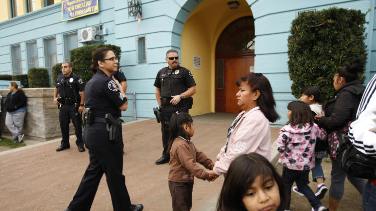 Los Angeles School Police officers provide security as parents and children gather outside of Miramonte Elementary school to protest as investigation continues into bizarre sexual abuse scandal in Los Angeles