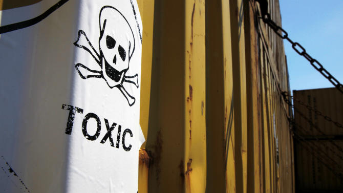 """In this photo taken on Tuesday, May 13, 2014, a sticker reading """"Toxic"""" on containers carrying Syria's dangerous chemical weapons, on the Danish cargo ship, Ark Futura, transporting the chemical weapons out of the strife-torn country, in Cyprus coastal waters. Organization for the Prohibition of Chemical Weapons director general Ahmet Uzumcu said Monday, June 23, 2014, the final shipment of stockpiled chemical weapons has been loaded onto Danish and Norwegian ships for transportation out of Syria.(AP Photo/Petros Karadjias)"""