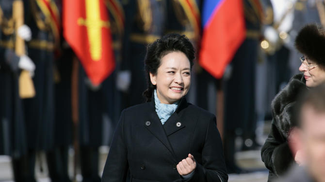 FILE - In this March 22, 2013 file photo, Chinese President Xi Jinping's wife Peng Liyuan smiles after arriving at the government airport Vnukovo II, outside Moscow, Russia. New Chinese first lady Peng is emerging as Chinese diplomacy's latest star. A well-known performer on state television, the glamorous Peng was featured prominently on Sunday's state media coverage of President Xi Jinping's activities in Russia. The visit is Xi's first since assuming the presidency earlier this month. (AP Photo/Ivan Sekretarev, File)