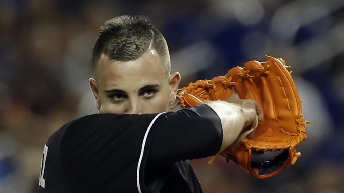 In this June 14, 2013 file photo, Miami Marlins' Jose Fernandez wipes his face during a baseball game against the St. Louis Cardinals in Miami. Fernandez won the NL Rookie of the Year On Nov. 11, 2013, making him the first Cuban to win the award since Jose Canseco in 1986. The announcement on Wednesday, Dec. 17, 2014 that the U.S. plans to restore diplomatic ties with the Caribbean nation could usher in a new era in U.S.-Cuba baseball relations, which were strained after the Castro revolution and the U.S.-led economic embargo