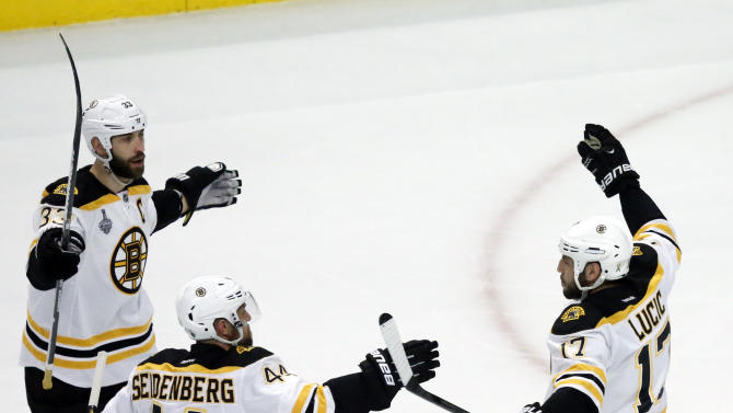 Boston Bruins left wing Milan Lucic (17) celebrates with defensemen Zdeno Chara (33) and Dennis Seidenberg (44) after scoring a goal against the Chicago Blackhawks during the first period of Game 1 in their NHL Stanley Cup Final hockey series on Wednesday, June 12, 2013, in Chicago. (AP Photo/Charles Rex Arbogast)