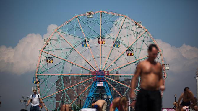 People at Coney Island in the Brooklyn borough of New York experience sunny weather while Hurricane Irene bears down on the eastern seaboard further south, Friday, Aug. 26, 2011. The low number of visitors at the typically crowded beach reflects the wind, rain, and flooding dangers the storm poses to the already saturated New York state. (AP Photo/John Minchillo)