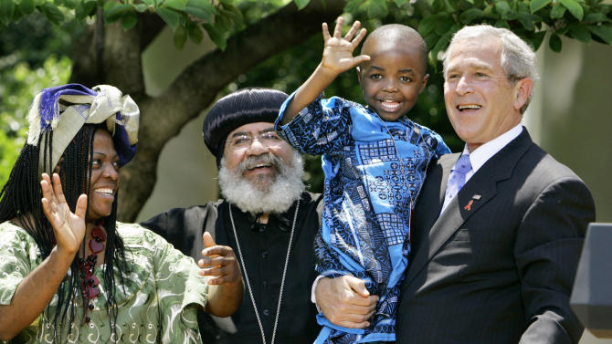 "FILE – In is May 30, 2007, file photo President Bush, right, hoists 4-year-old Baron Mosima Loyiso Tantoh, son of Manyongo Mosima ""Kuene"" Tantoh of South Africa, left, who is HIV-positive, after speaking about his efforts to fight HIV/AIDS worldwide, in the Rose Garden of the White House in Washington. At center is Coptic Orthodox Church Bishop Paul Yowakim of Kenya. The decade-old law that transformed the battle against HIV/AIDS in developing countries is at a crossroads, the dream of future generations freed from epidemic running up against an era of economic recovery and harsh budget cuts. The President's Emergency Plan for AIDS Relief grew out of an unlikely partnership between Bush and lawmakers led by the Congressional Black Caucus, and has come to represent what Washington can do when it puts politics aside_and what America can do to make the world a better place. (AP Photo/J. Scott Applewhite, File)"