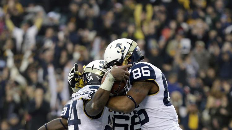 Navy's Noah Copeland, from left, Ryan Paulson and Brandon Turner celebrate after Copeland's rushing touchdown during the first half of an NCAA college football game against Army, Saturday, Dec. 8, 2012, in Philadelphia. (AP Photo/Matt Slocum)