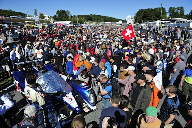 Fans take pictures of the pole sitting Peugeot car before the American Le Mans Series' Petit Le Mans auto race at Road Atlanta, Saturday, Oct. 1, 2011, in Braselton, Ga.  (AP Photo/Rainier Ehrhardt)