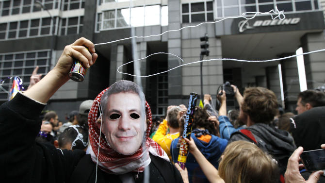 A protester wearing mask of Chicago Mayor Rahm Emanuel, shoots out silly string during a demonstration outside Boeing corporate offices Monday, May 21 2012, in Chicago, on the final day of the NATO summit. (AP Photo/Charles Rex Arbogast)