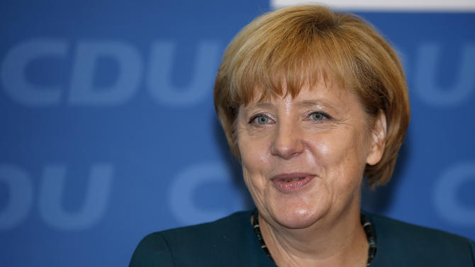 German Chancellor and chairwoman of the German Christian Democratic party, CDU, Angela Merkel, smiles as she arrives for a party's board meeting in Berlin, Monday, Sept. 23, 2013. Top party officials are meeting to talk strategy about reaching out to the center-left rivals they need to form a government, after Merkel won a stunning victory in Germany's elections on Sunday. (AP Photo/Michael Sohn)