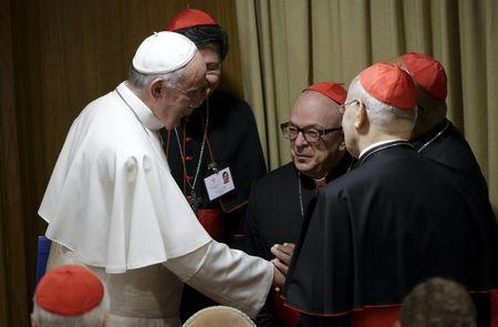 Pope Francis talks with cardinals as he leads the synod on family in the Synod hall at the Vatican