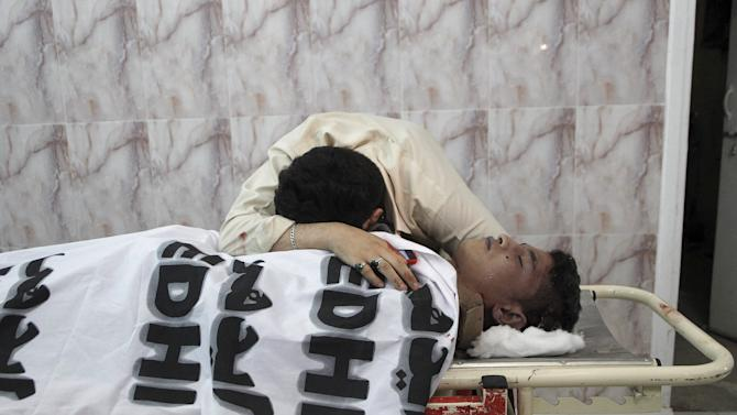 A man reacts over to the body of a relative, who was killed with two others by unidentified gunmen, in a hospital Quetta