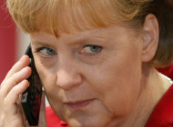 FILE - In this March 4, 2008 file photo German Chancellor Angela Merkel speaks on a mobile phone during her opening walk at the CeBIT in Hanover, northern Germany. Merkel, currently on vacation in Italy, will hold a telephone conference Friday, Aug. 5, 2011, with French President Nicolas Sarkozy as stock markets around the world on a combination of worries over the U.S. economy and Europe's debt crisis. (AP Photo/Kai-Uwe Knoth, File)