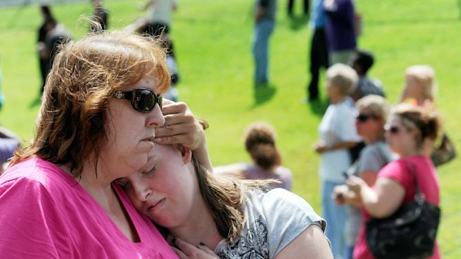 Tracie Bradford, of Perry Hall, Md., consoles her daughter Leah, a student at Perry Hall High School who says she was in the school's cafeteria when a student was shot there and critically wounded on the first day of classes, Monday, Aug. 27, 2012, in Perry Hall, Md. A suspect was taken into custody shortly after the shooting, according to police. No one else was reported injured. (AP Photo/Steve Ruark)