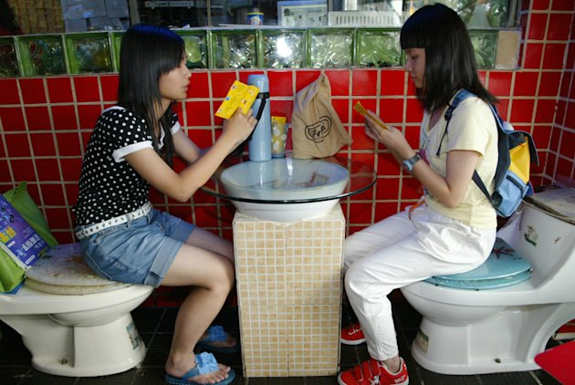 Para pelanggan melihat daftar menu sambil duduk di atas dudukan toilet di restoran bertema toilet di Shenzhen, Provinsi Guangdong, di Cina selatan, 22 Oktober 2006. CHINA OUT REUTERS/Joe Tan