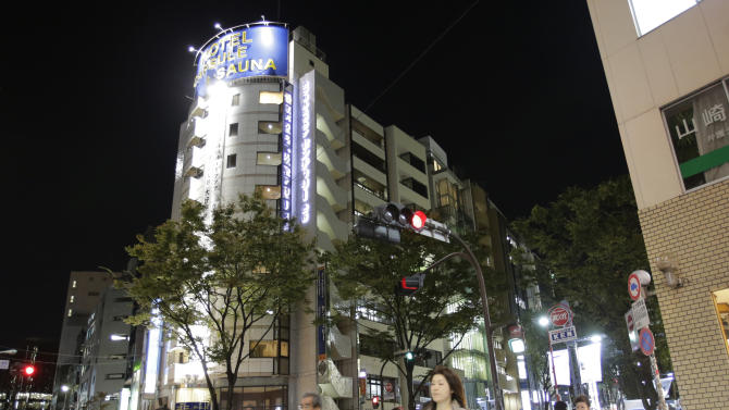 In this Monday, Oct. 29, 2012 photo, people walk by the Capsule & Sauna Century Shibuya, a building at center, in Tokyo. The capsule concept has been around for at least 30 years, starting out as lodging for businessmen working or partying late who missed the last train home and needed a cheap place to crash. But budget travelers and other folks curious about a unique lodging experience use them too. (AP Photo/Shizuo Kambayashi)