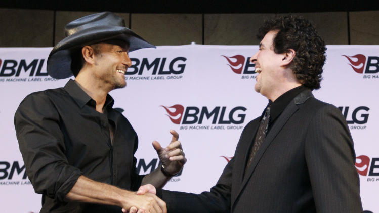 Country music star Tim McGraw, left, shakes hands with Scott Borchetta, right, president of Big Machine Records, after a news conference at the Country Music Hall of Fame and Museum on Monday, May 21, 2012, in Nashville, Tenn. McGraw and Borchetta announced McGraw has signed a multi-album deal with Big Machine Records, officially ending his rocky relationship with his only previous label, Curb Records. (AP Photo/Mark Humphrey)