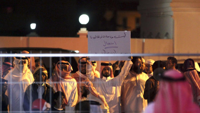 """Bahraini protesters chant slogans and one holds a banner that reads, """"none of our customs and traditions allow us to receive stars of porn movies,"""" referring to TV star Kim Kardashian, in Riffa, Bahrain, Dec. 1, 2012. Just hours after reality TV star Kim Kardashian gushed about her impressions of Bahrain, riot police fired tear gas to disperse more than 50 hardline Islamic protesters denouncing her presence in the Gulf kingdom .(AP Photo/Hasan Jamali)"""