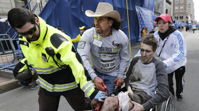 FILE - In this Monday, April 15, 2013, file photo, Boston EMT Paul Mitchell, left, bystander Carlos Arredondo, in cowboy hat, and Boston University student Devin Wang push Jeff Bauman in a wheelchair after he was injured in one of two explosions near the finish line of the Boston Marathon. Bauman and his three rescuers, became one of the most recognizable and powerful symbols of Boston's resilience after the April 15 attacks. (AP Photo/Charles Krupa)