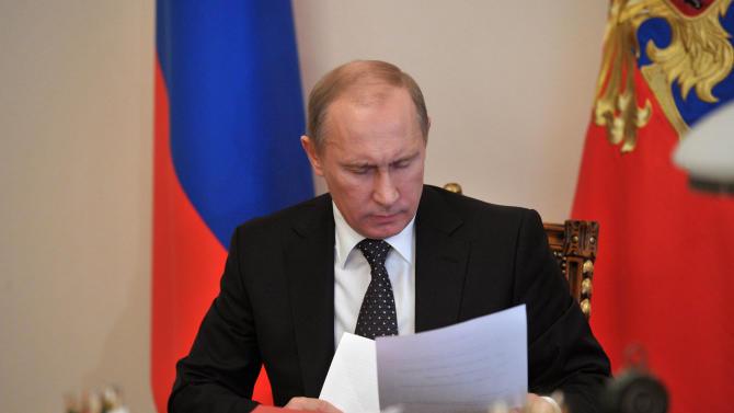 Russian President Vladimir Putin reads papers at his study at the Novo-Ogaryovo residence outside Moscow, Friday, Nov. 2, 2012. (AP Photo/RIA Novosti, Alexei Nikolsky, Presidential Press Service)