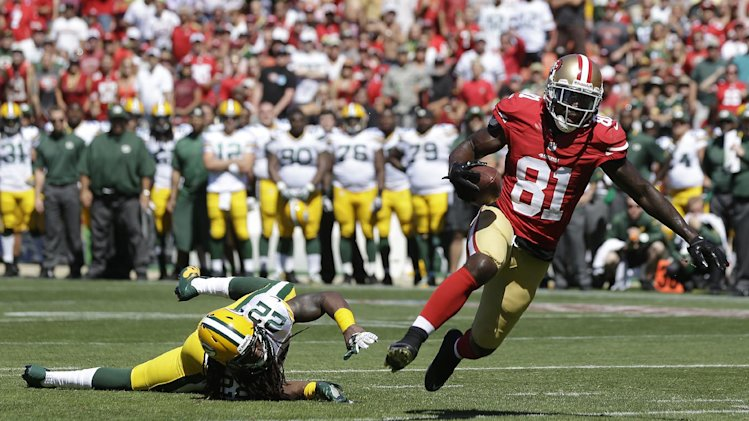 San Francisco 49ers wide receiver Anquan Boldin (81) scores on a 10-yard touchdown reception against past Green Bay Packers defensive back Jerron McMillian (22) during the second quarter of an NFL football game in San Francisco, Sunday, Sept. 8, 2013