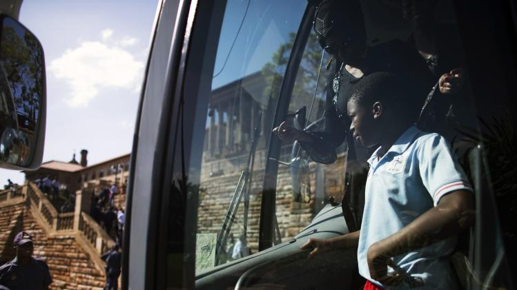A boy waits inside a bus as he arrives at Union Buildings in Pretoria, where the body of Nelson Mandela is lying in state
