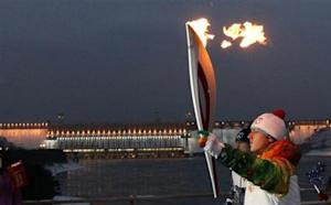 A runner carries the Sochi 2014 Winter Olympic torch in Krasnoyarsk