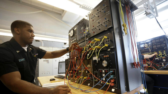 In this Thursday, Oct. 8, 2015, photo, Massachusetts Maritime Academy senior Kervin Claude, of Boston, works in a electrical machine laboratory on the schools campus, in Bourne, Mass. Two of the missing crewmen who were aboard the 790-foot cargo ship El Faro that Hurricane Joaquin sank in the Bahamas were graduates of the Massachusetts Maritime Academy. (AP Photo/Steven Senne)