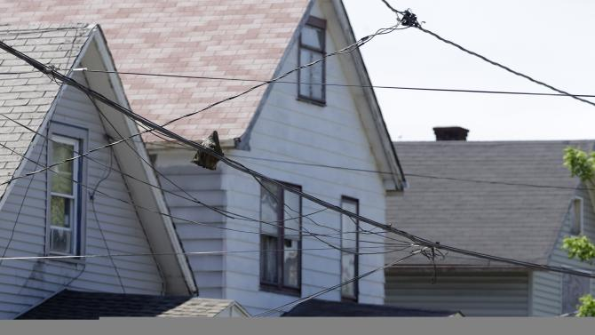 A law enforcement officer walks past the house where three women missing for about a decade were found alive,  in Cleveland,  Thursday, May 9, 2013.  Ariel Castro was charged with kidnapping and rape while his brothers, Pedro and Onil Castro, were arrested and cleared without charges. (AP Photo/David Duprey)