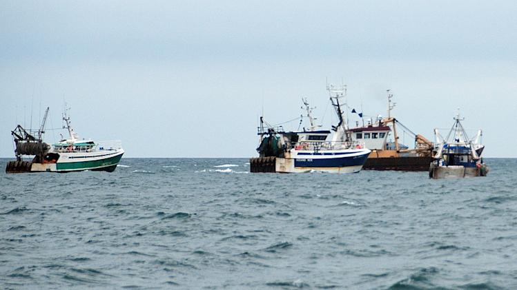This Oct. 8, 2012 photo shows, British fish boats left and right,  being prevented to fish by French fishermen, in the English Channel, off Le Havre, western France. A bumper season for the French national dish of Coquilles St. Jacques has turned into a bitter dispute in the English Channel, as French fishermen angry over British expansion into their waters surrounded British boats in a show of maritime force.(AP Photo/Pierre Guillaume)
