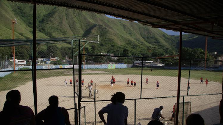In this Oct. 25, 2012 photo, people watch their children attend a baseball school in Maracay, Venezuela. Many of the boys are inspired by the example of Detroit Tigers slugger Miguel Cabrera, who learned the game on this very field. Their baseball school in the poor neighborhood where Cabrera grew up is one of many across Venezuela, a web for training young ballplayers that has made the country a powerhouse in the U.S. major leagues. (AP Photo/Ariana Cubillos)