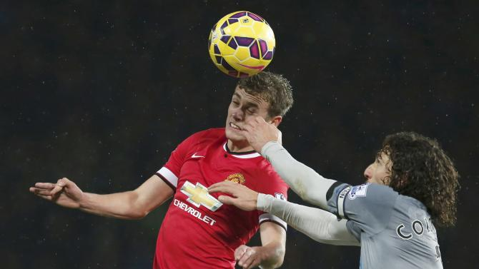 Manchester United's James Wilson is challenged by Newcastle United's Fabricio Coloccini during their English Premier League soccer match at Old Trafford in Manchester