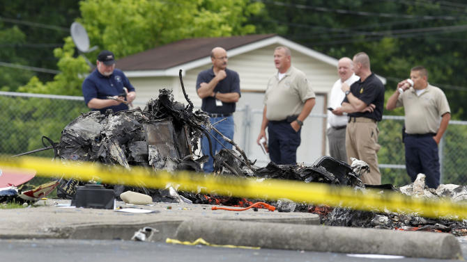 "Officials looked over debris at the scene of a Thursday evening helicopter crash that killing all three Air Evac Lifeteam crewmembers aboard, in the parking lot next to Paces Elementary School in Manchester, Ky., Friday, June 07, 2013. The company identified the crewmembers as pilot Eddie Sizemore, flight paramedic Herman ""Lee"" Dobbs and flight nurse Jesse Jones. There was no patient on board. (AP Photo/Lexington Herald-Leader, Charles Bertram)"