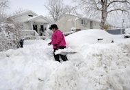 April Palmieri digs out her car in front of her home, background left, on 17th Street after a snow storm on Saturday, Feb. 9, 2013 in Bayville, N.Y. Palmieri had five feet of water in her basement as result of the rains from Superstorm Sandy. A howling storm across the Northeast left the New York-to-Boston corridor shrouded in 1 to 3 feet of snow Saturday, stranding motorists on highways overnight and piling up drifts so high that some homeowners couldn&#39;t get their doors open. More than 650,000 homes and businesses were left without electricity. (AP Photo/Kathy Kmonicek)