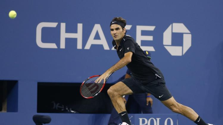 Roger Federer of Switzerland chases down a ball from Roberto Bautista Agut of Spain during their men's singles match at the 2014 U.S. Open tennis tournament in New York