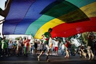 Israelis carry a rainbow coloured flag as they participate in the 10th anniversary Gay Pride Parade in Jerusalem